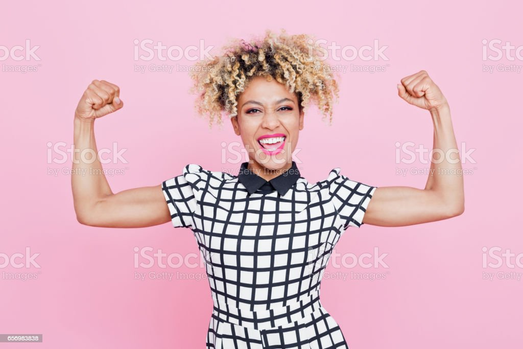 Happy afro american young woman flexing arms Studio portrait of excited afro american young woman flexing her muscles. Pink background. 20-24 Years Stock Photo