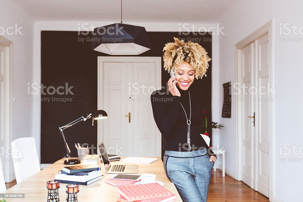 Happy afro american young woman in a home office Beautiful afro american young woman in a home office, talking on mobile phone. Adult Stock Photo