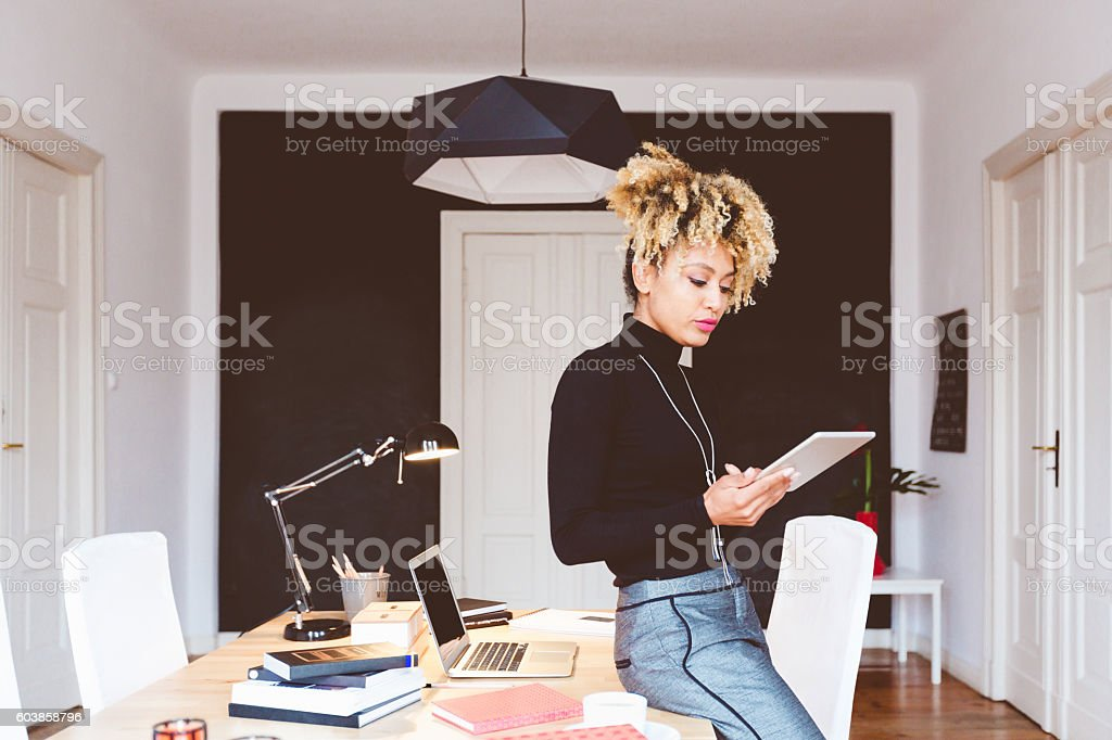Happy afro american young woman in a home office Beautiful afro american young woman in a home office, using a mobile device. Adult Stock Photo