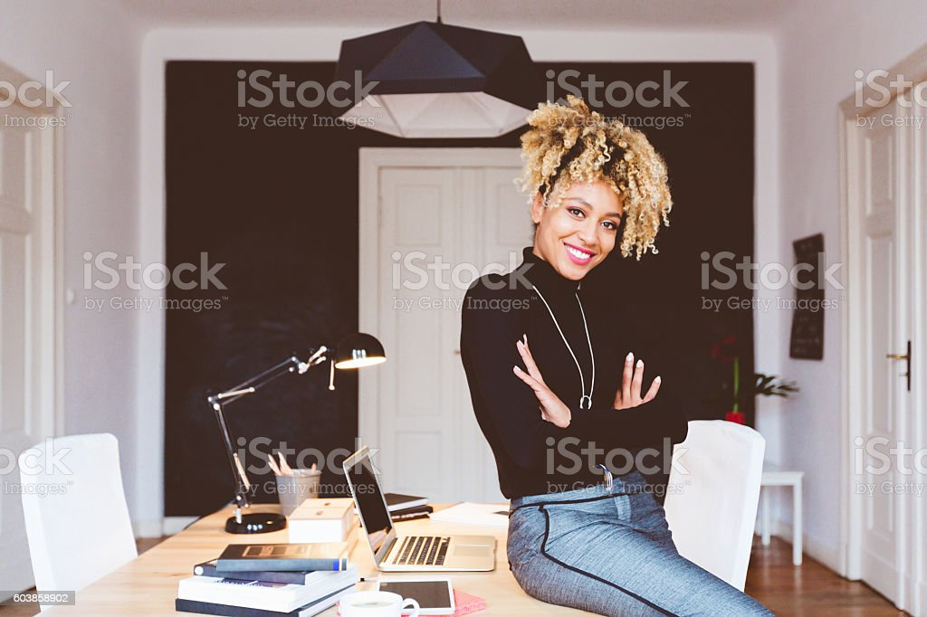 Happy afro american young woman in a home office Beautiful afro american young woman in a home office, smiling at camera. Adult Stock Photo