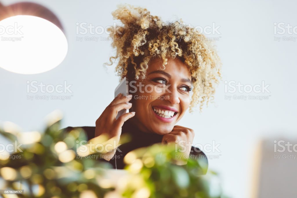 Happy afro american young woman talking on smart phone Beautiful afro american young woman talking on mobile phone indoors. Adult Stock Photo