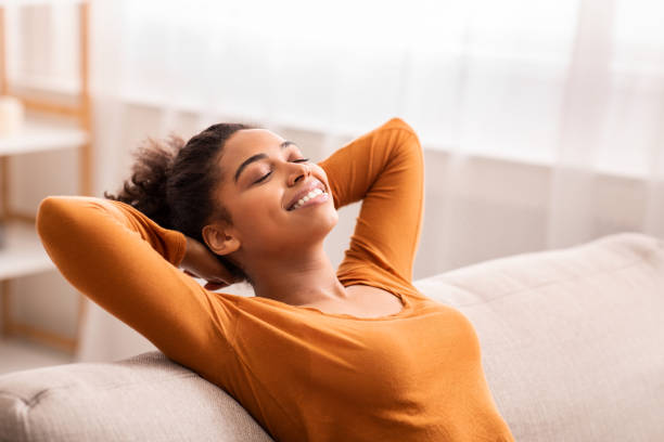 Happy Afro Girl Relaxing Sitting On Couch At Home stock photo