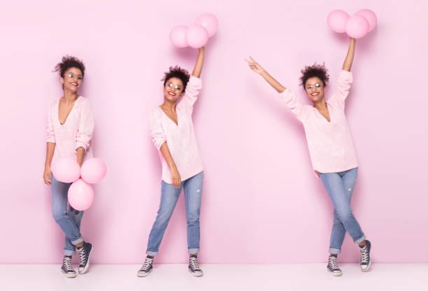 fröhliches afro mädchen mit erstaunlichen lächeln posiert auf rosa hintergrund. - ballonhose stock-fotos und bilder