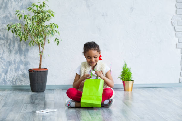 fröhliches afro mädchen mit einkaufstüten - laminat günstig stock-fotos und bilder