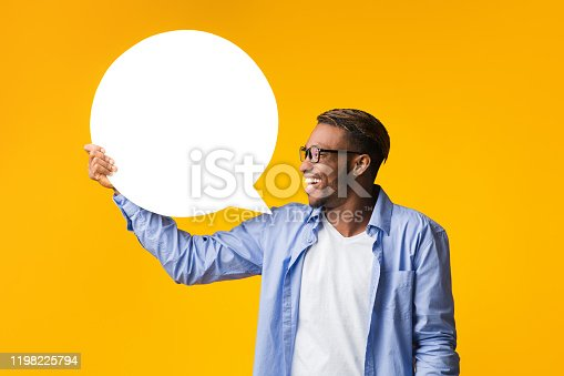 istock Happy Afro Guy Holding Blank Speech Bubble Standing, Yellow Background 1198225794