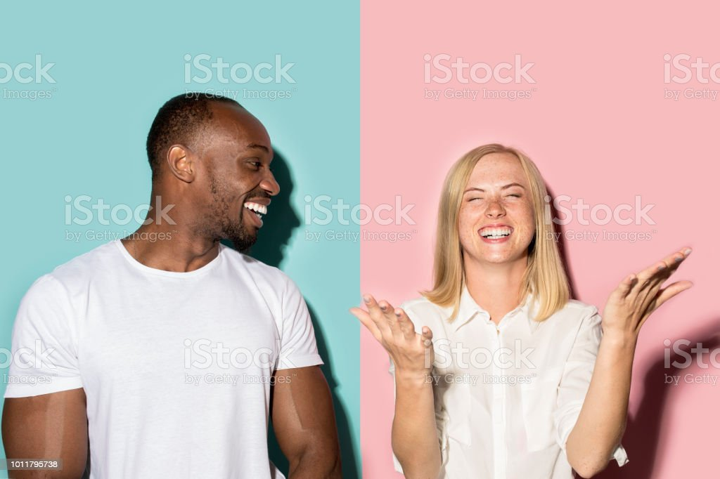 happy afro man and woman. Dynamic image of caucasian female and afro male model on pink studio royalty-free stock photo