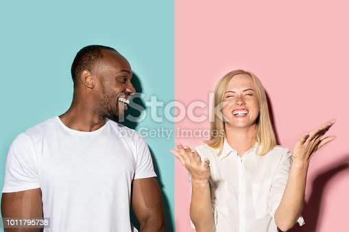 istock happy afro man and woman. Dynamic image of caucasian female and afro male model on pink studio 1011795738