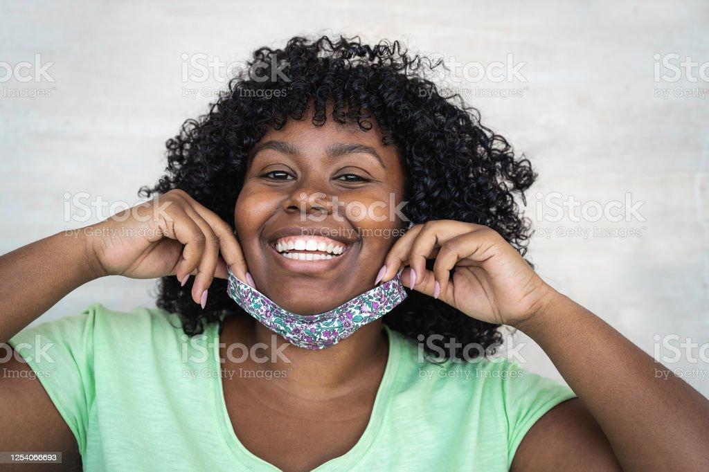 해피 아프로 여성 초상화 - 카메라 앞에서 미소 짓는 얼굴 마스크를 착용한 아프리카 소녀 - 건강 관리 및 코로나 바이러스 발병 개념 - 로열티 프리 COVID-19 스톡 사진