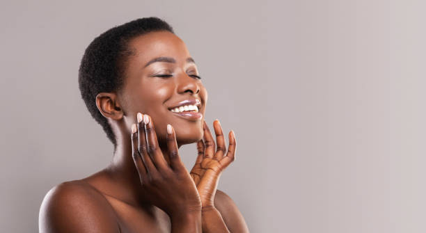happy afro woman touching soft smooth skin on her face - beauty foto e immagini stock