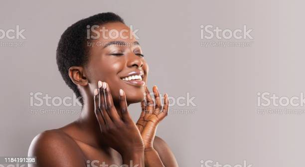 Photo of Happy afro woman touching soft smooth skin on her face