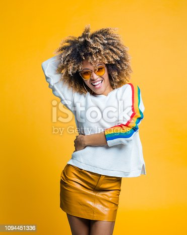 521083232istockphoto Happy afro young woman dancing against yellow background 1094451336