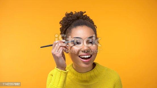 Happy Afro-American lady applying eye shadows, visage master class, beauty