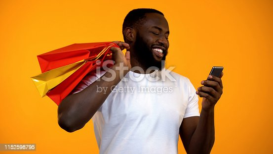 istock Happy Afro-American man holding shopping bags and smartphone, online purchase 1152598795