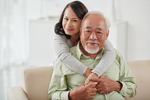 Happy aged couple Happy smiling aged woman hugging her husband from behind vietnamese ethnicity stock pictures, royalty-free photos & images