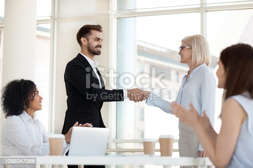 1016196912 istock photo Happy aged executive handshaking successful employee congratulating with job promotion 1095047058