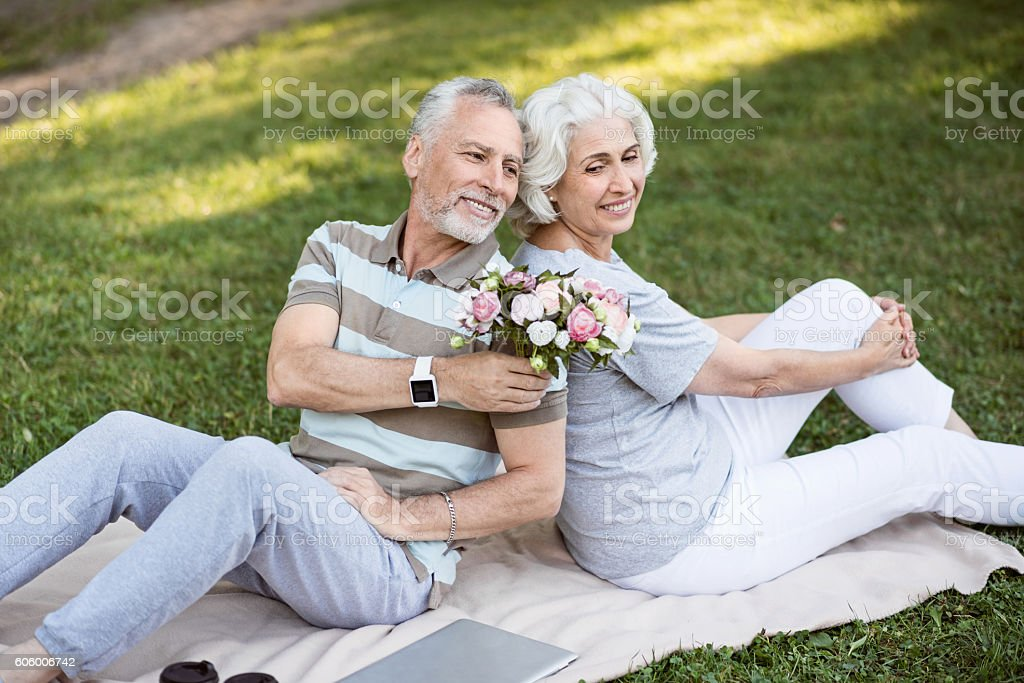 Happy aged married couple sitting on the grass in park - foto de acervo