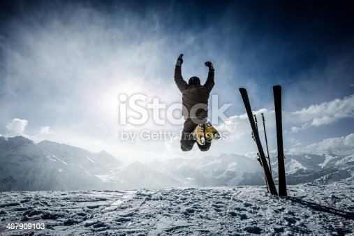 istock Happy alpine skier jumping in air on the top 467909103