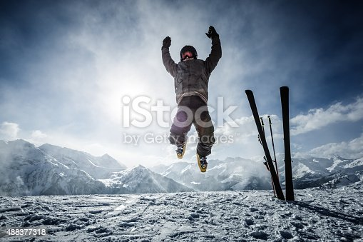 istock Happy alpine skier jumping in air on the top 488377318