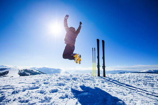 istock Happy alpine skier jumping in air on the top 493439318