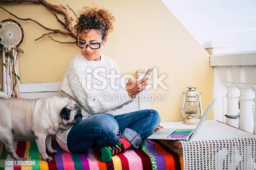 Happy alternative young cheerful woman working at home with a new business way. sitting on a bench outdoor at home with best friend old pug together. colorful bench and lifestyle. laptop and phone to communicate and internet