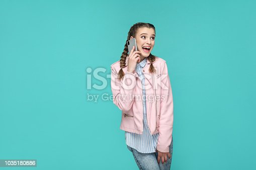 happy amazed beautiful girl in casual style, pigtail hairs, standing and speaking with mobile smart phone and looking away with surprised face, Indoor studio shot isolated on blue or green background