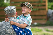 Military man father hugs son. Portrait of happy american family. focus on fathers back