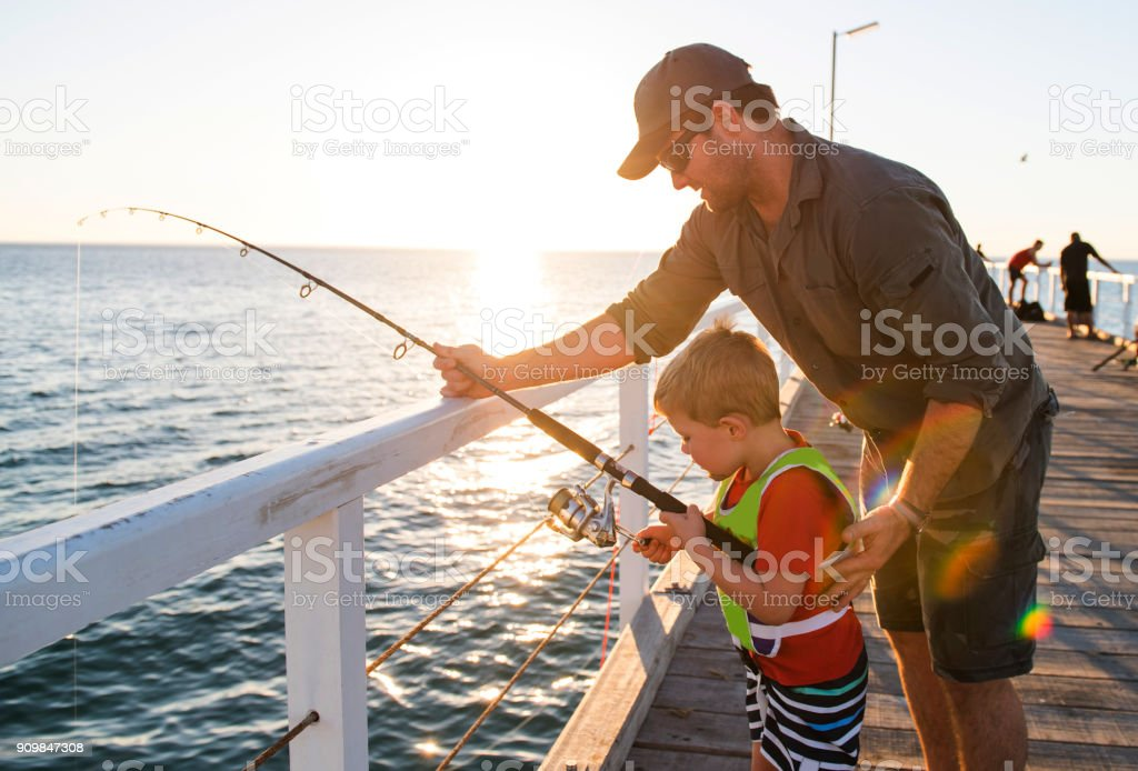 happy American father teaching little young son to be a fisherman, fishing together on sea dock embankment enjoying and learning using the fish rod on a sunny Summer day stock photo