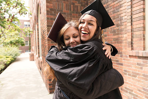 Happy American Mother Hugs Daughter Celebrating Graduation Day USA stock photo