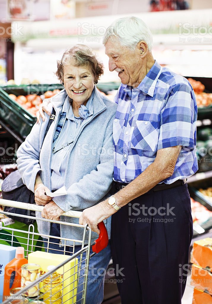 Happy and affectionate senior couple shopping in supermarket stock photo