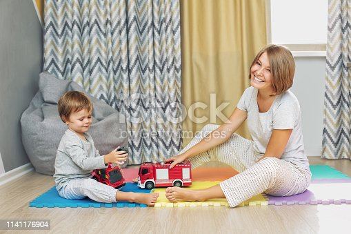 istock Happy and beautiful mother and child, family together playing toy cars in the nursery 1141176904
