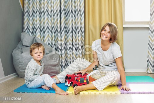 istock Happy and beautiful mother and child, family together playing toy cars in the nursery 1141179015