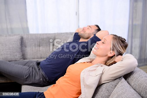 istock happy and beautiful young couple resting and meditating on the sofa at home 936098438