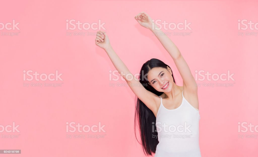 Happy and cheerful smiling Asian 20s woman raising hands up for positive feeling and celebration isolated over pink background. stock photo