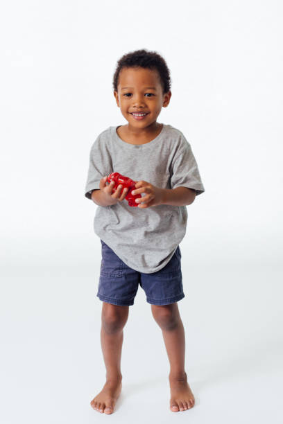 Happy and cute African American boy playing his toy isolated in white background stock photo