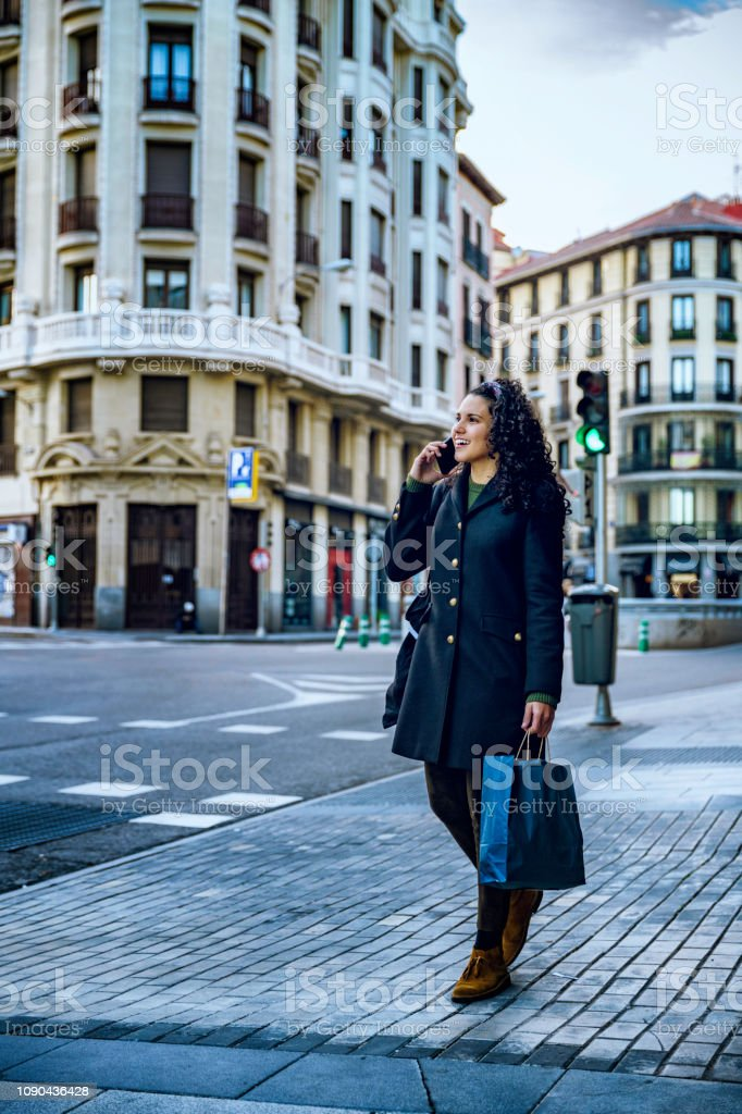 Happy and elegant Hispanic young woman using smart phone in the...