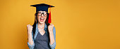 Happy and excited portrait of young student girl in hat of graduation