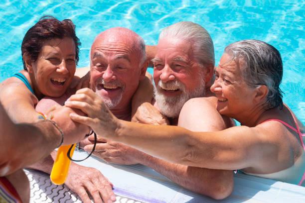 glückliche und lustige gruppe von senioren im schwimmbad genießen den sommer und ruhestand. glück unter der strahlenden sonne. blaues transparentes wasser - senior bilder wasser stock-fotos und bilder