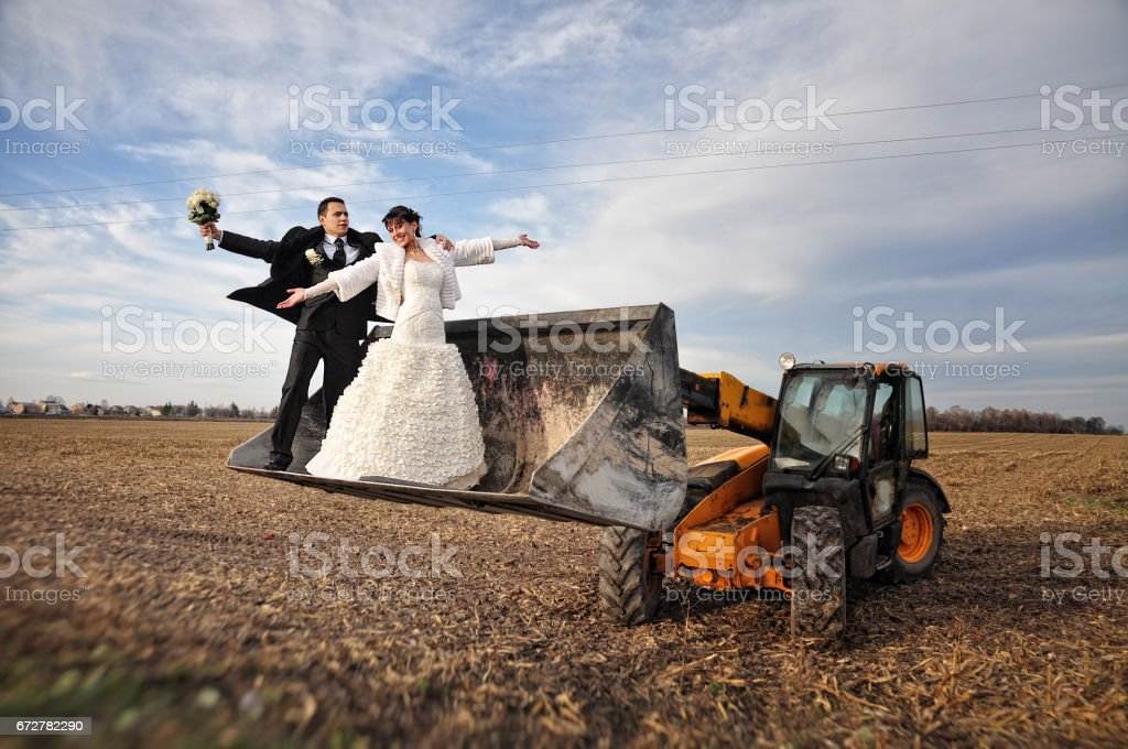 Happy and funny wedding couple in a scoop tractor stock photo