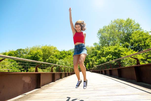 Glückliche und lustige junge Frau springt auf einer Brücke in einem sonnigen Tag – Foto