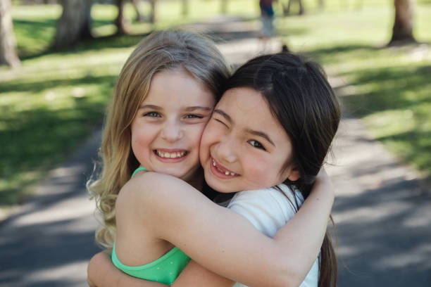 Happy and healthy mixed ethnic young little girls hugging and smiling in the park, best friends and friendship concept stock photo