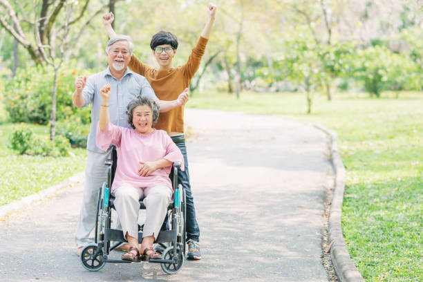 happy and joyful Asian family in the park Shot of a happy and joyful Asian family celebrated success with arms up. Senior woman in a wheelchair with her husband and son at the park old mother son asian stock pictures, royalty-free photos & images