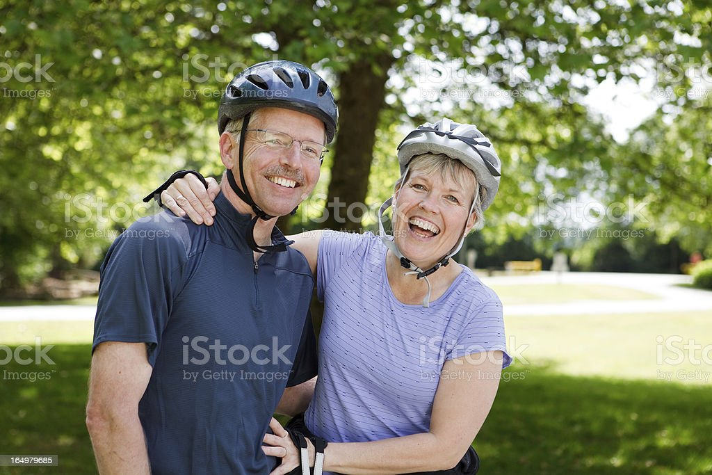 Happy and laughing couple outside rollerblading wearing helmets stock photo