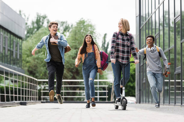 happy and positive teenagers smiling, running and riding scooter happy and positive teenagers smiling, running and riding scooter teenagers only stock pictures, royalty-free photos & images