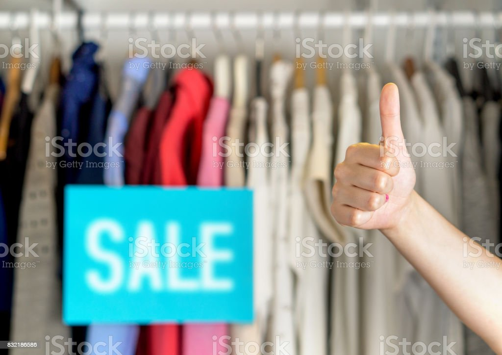 Happy and satisfied customer giving thumbs up in a clothing store for good service or great product quality. Pleased shopper in fashion clothes store showing positive hand gesture. stock photo