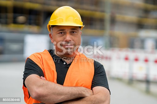 istock Happy and satisfied engineer with crossed arms on construction site 855536446