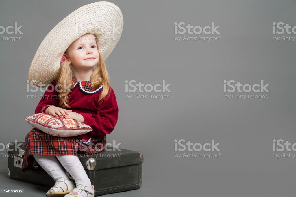 ff37a302120 Happy And Smiling Caucasian Child Posing in Big Round Sombrero Hat and  Sitting on Outdated Suitcase. - Stock image .