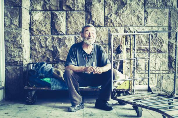 glücklich und lächelnd armen obdachlosen im schatten des gebäudes auf der städtischen straße in der stadt sitzen und trinken alkohol trinken aus kleinen flasche - dokumentation stock-fotos und bilder