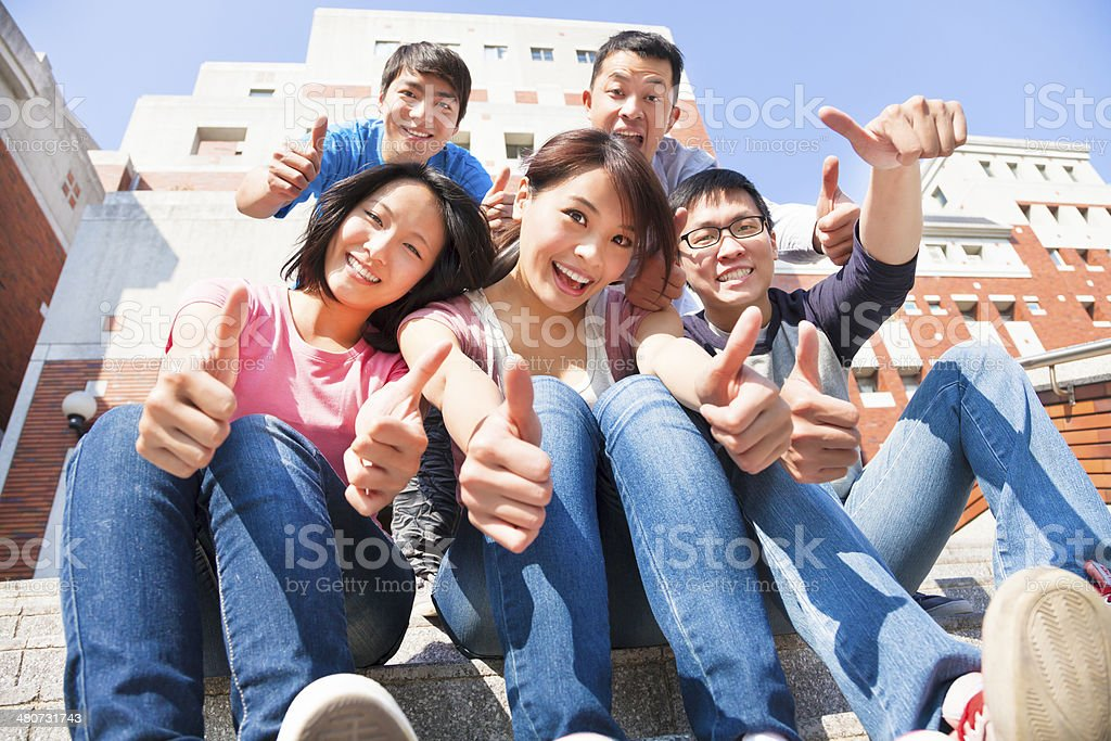 happy and smiling students thumbs up  together stock photo