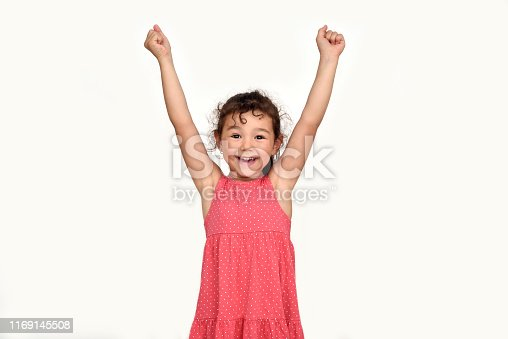 istock Happy and smiling young girl with hands up 1169145508