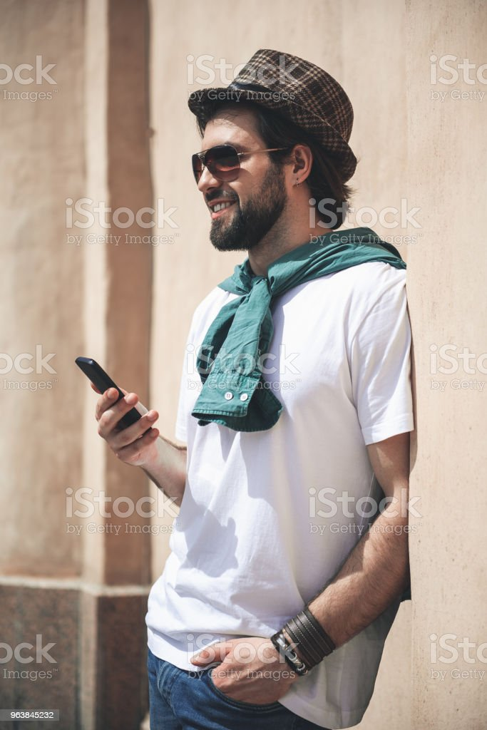 Happy and stylish man using smartphone while standing alone - Royalty-free Adult Stock Photo